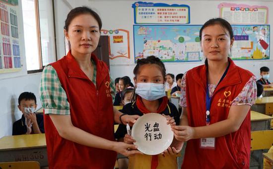 """社区志愿者指导同学在自带光盘上写上""""光盘行动""""的字句"""