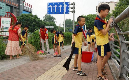 郴州市十八完小20多位学生与街道机关的叔叔阿姨们一道清扫下湄桥桥面、擦拭桥栏杆