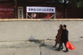 """12月6日,长沙湘江中路,文和友老长沙龙虾馆在水泥墙后打出""""正常营业""""的牌子,以吸 引食客就餐。组图/记者金林辜鹏博谢长贵"""