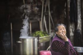 11月3日,长沙半湘街社区,老街巷旁冒着热气的店面和坐在巷子里发呆的老人。