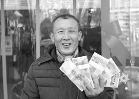2月7日,65岁的郑湘午用从法院领到的支票在银行换到钱后,非常开心。 图/记者华剑