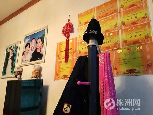 ▲李晖家中墙上挂着一家三口的合影和儿子的奖状 记者 戴凛 摄
