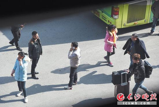 昨日中午,数名拉客人员在汽车西站公交站内招揽过往乘客。多名在岳麓大道上候车的外地乘客反映,他们就是被这些拉客人员送到了那里。  长沙晚报记者 余劭劼 摄