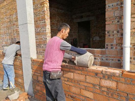 """右臂残缺的胡元清正在砌砖。网友""""永州号外"""" 摄"""