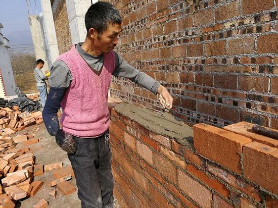 """右臂残缺的建筑农民工胡元清正在砌砖。网友""""永州号外"""" 摄"""