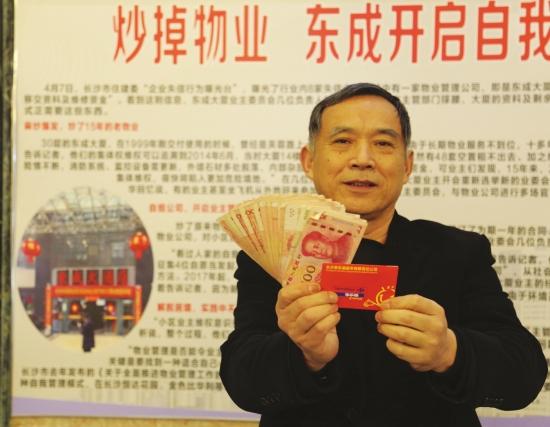 2月9日,长沙东成大厦,物业人员展示自己领到的奖金和500元购物卡。图/记者金林实习生张云峰