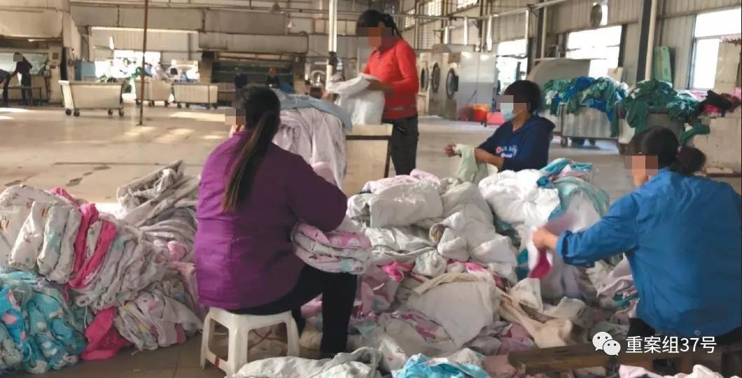 11月30日,南昌市丰源洗衣中心内,工人们正将堆放在地面的江西省儿童医院婴儿医用布草进行折叠打包。现场环境脏乱,婴儿布草在洗涤烘干后被随意堆放在地面。 新京报记者 尹亚飞 摄