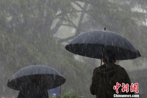 9日上午,南京突降雷暴大雨。图为市民用各色雨伞遮挡大雨。 泱波 摄