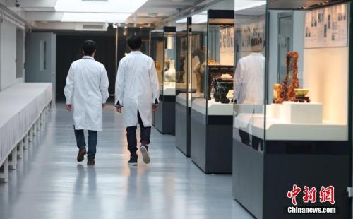 """资料图:两名""""文物修复医生""""在故宫文物医院内走过。中新社记者 杨可佳 摄"""