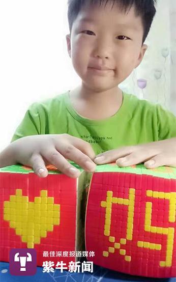 刘怡昊自己摸索魔方拼字。