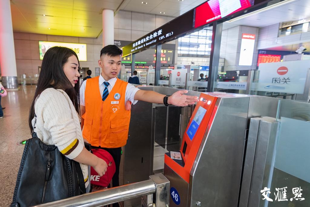 上海虹桥站工作人员在引导旅客使用自助实名制核验闸机。 李忱 摄