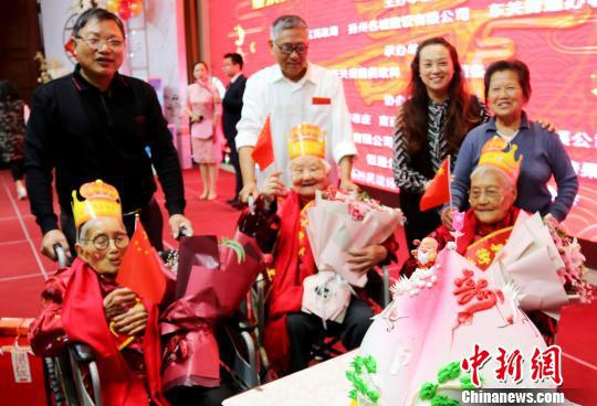 图为当地民众向百岁老人贺寿。 施华健 摄