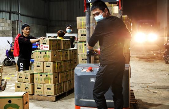 ▲合并后,团队的订单量直线上涨,店铺工作人员正连夜打包发货。(覃凡 摄)