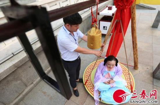 在西安大唐芙蓉园西门外,众多女士用杆秤称体重,只要体重够61.8公斤,就会被景区认定为最美唐妞,可换门票一张免费游览大唐芙蓉园。三秦网 图