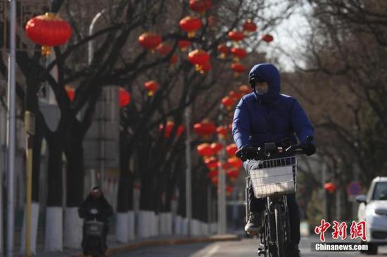 资料图:市民保暖出行。中新社记者 蒋启明 摄
