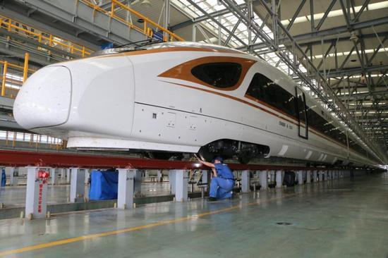 """图为CR400BF-A型长编组""""复兴号""""动车组列车驶入虹桥动车所检车库。"""