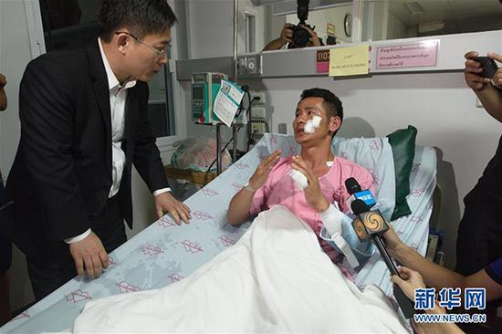 7月7日凌晨,在泰国普吉岛,翻船事故幸存者黄俊雄向中国驻泰国大使吕健(左)回忆逃生经历。