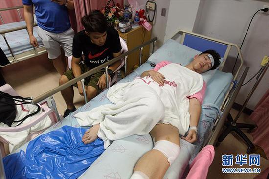 7月7日凌晨,在泰国普吉岛,翻船事故幸存者林宏政(左)在病房照顾受伤的同学。