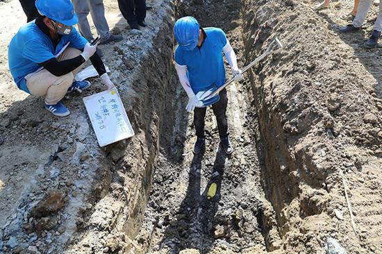 第三方检测机构工作人员对疑似掩埋化工废料处进行取样。澎湃新闻记者 廖文君 图
