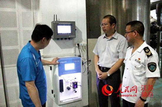 图为江苏省卫生监督所行政执法指挥中心工作人员在现场检测游泳池水的指标。