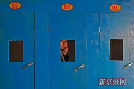 ▲2014年6月2日,一位女同学在校外的电话亭打电话。毛坦厂中学禁止学生带手机。