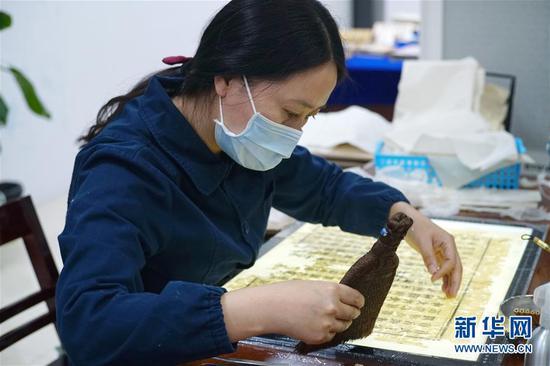 """11月29日,在四川省古籍修复中心,""""古籍医生""""对需要托裱的书页刷浆糊。"""