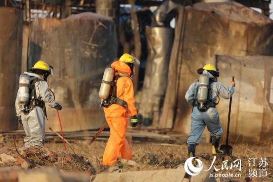 身着防化服的消防队员在废墟中搜寻马焘焘 摄