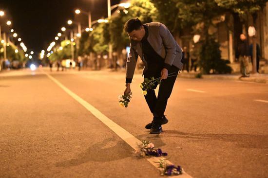 在车队到来之前,当地群众在街道中间摆上鲜花祭奠英雄。