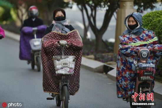 """资料图:天气降温,早高峰上班出行的人们""""全副武装"""",从头到脚裹得严严实实。图片来源:IC photo"""