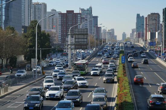 """东三环主路上,南向北方向道路内各类机动车拥挤到""""完全不动""""。摄影/新京报记者 裴剑飞"""