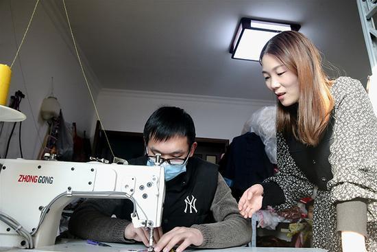 任赛男和制衣师傅沟通寿衣款式。