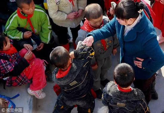 ▲图文无关,图为某老师一边训斥学生,一边举手敲打学生的脑袋。图/视觉中国