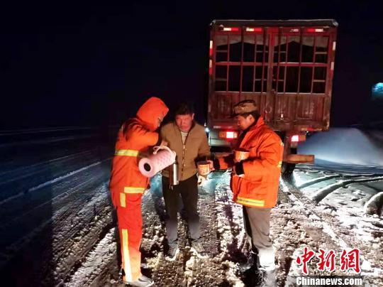 图为公路部门职工为卡车司机送方便面。李学鹏 摄