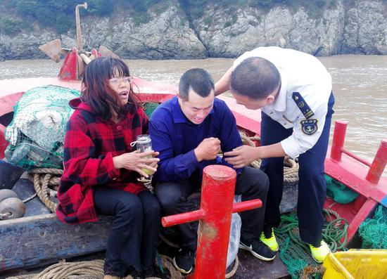 救援人员在安抚获救的船员夫妻俩。李昊 图
