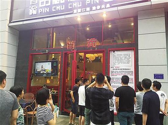 餐馆门口张贴的千字海报引路人围观。张宇 图
