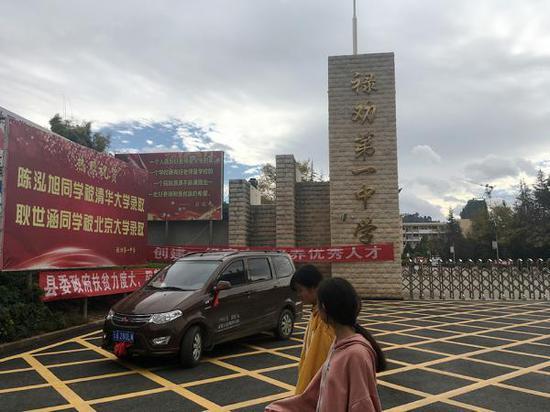禄劝县第一中学门口,竖立的牌子上是被清华、北大录取的两名同学的名字