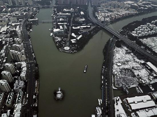 京杭大运河中的货船驶过黄埠墩。