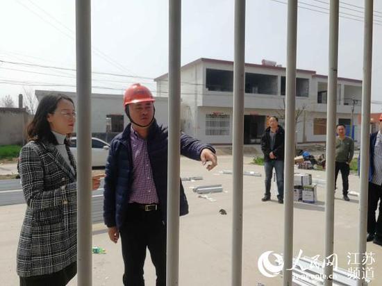 陈家港镇党委副书记罗爱华(左)现场检查受损民房修缮情况。记者王继亮摄