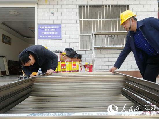 援建工人在测量新定制的门窗。记者王继亮摄