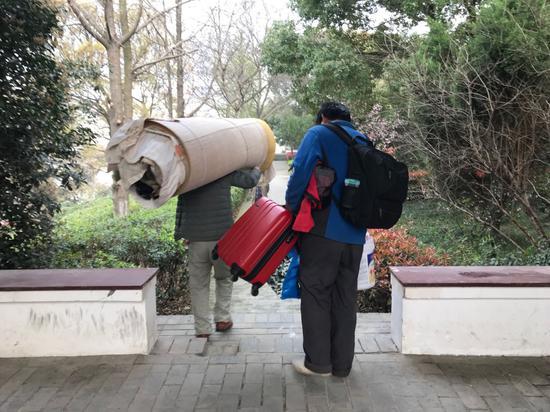 被劝离后,朱路路(右)将行李从墓园搬走。新京报记者祖一飞摄