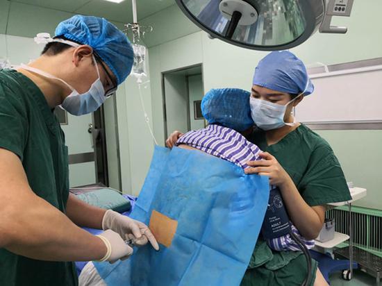 护士将170斤中产妇抱着让医生完成麻醉手术。 袁敏 摄