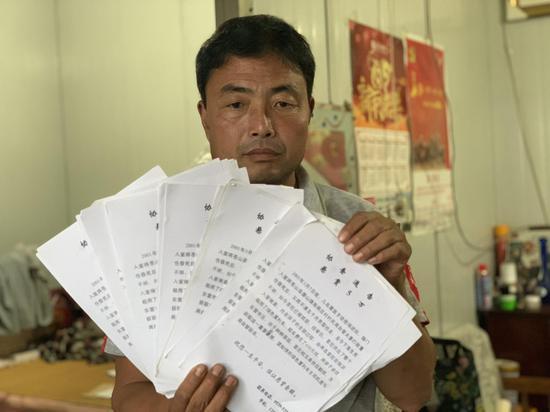 7月6日,被抢男孩父亲翻出寻找孩子的告示。新京报记者 左燕燕 摄