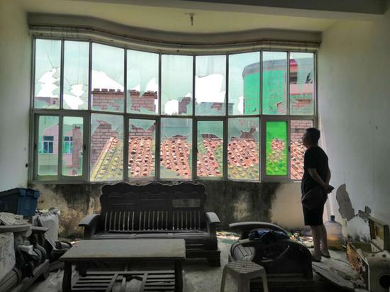 念斌站在被打砸一空的老屋玻璃窗前。