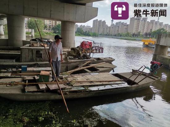 记者遇到何师傅在岸边用竹篙撑船