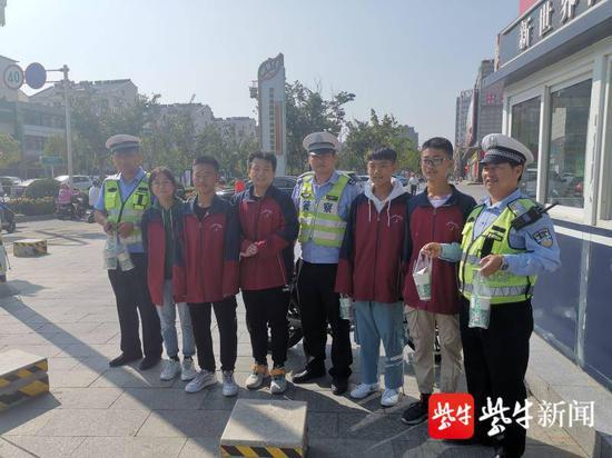节日期间坚守岗位的民警、辅警手拿奶茶与学生们合影