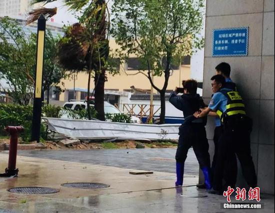 福建省宁德市区,记者在风雨中进行直播。林冬冬 摄