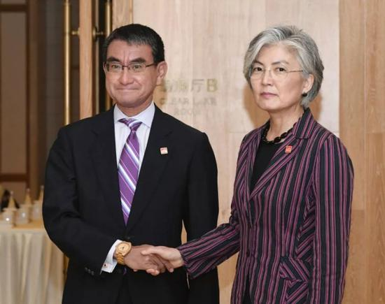 韩国外交部长官康京和(右)和日本外相河野太郎在进行双边会晤前握手合影。