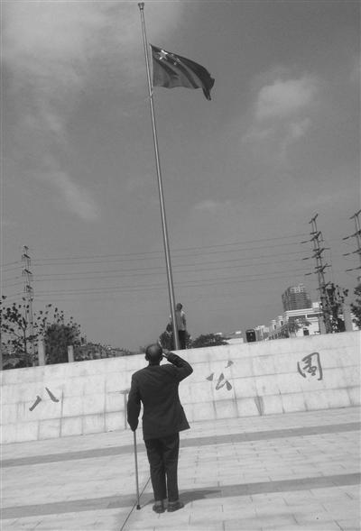 八一广场上,国旗升起,孙运华敬礼。