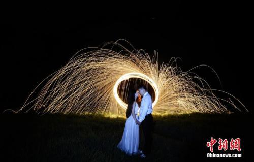 资料图:一对情侣在飞溅的火花下深情目视对方。 杨华峰 摄