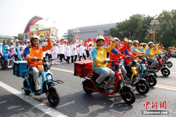 """10月1日上午,庆祝中华人民共和国成立70周年大会在北京天安门广场隆重举行。图为群众游行中的""""快递小哥""""。 本文图均为 中新网 图"""